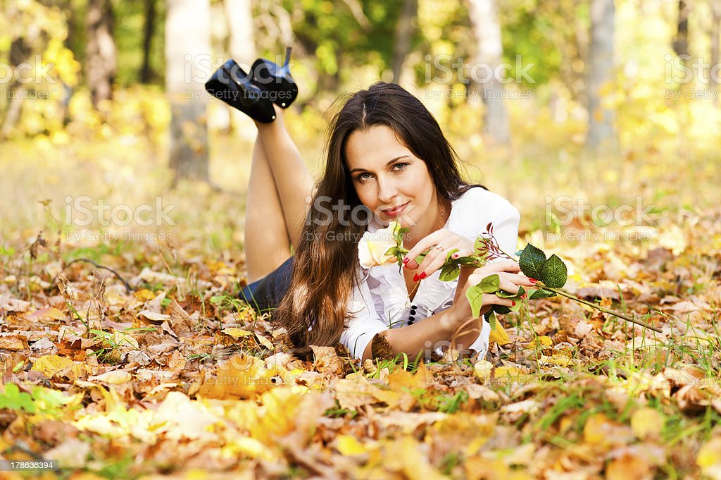 woman lying on the autumn leaves royalty-free stock photo