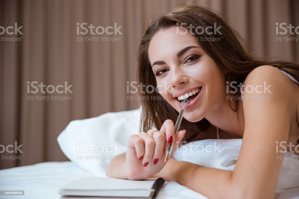 Woman lying on the bed with pen and notepad stock photo