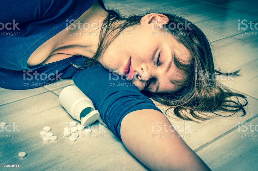 Woman lying on the floor after an overdose of pills stock photo