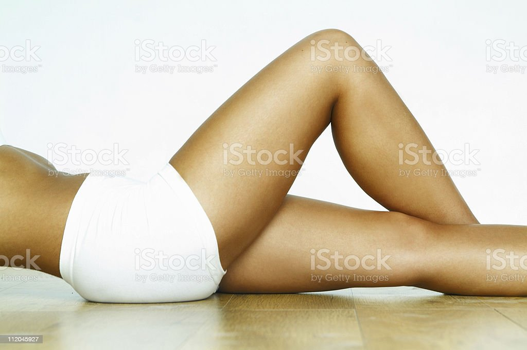 Woman lying on the floor exercising with white shorts on royalty-free stock photo