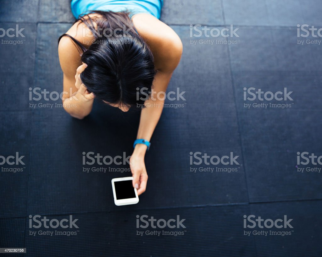 Woman lying on the floor with smartphone stock photo