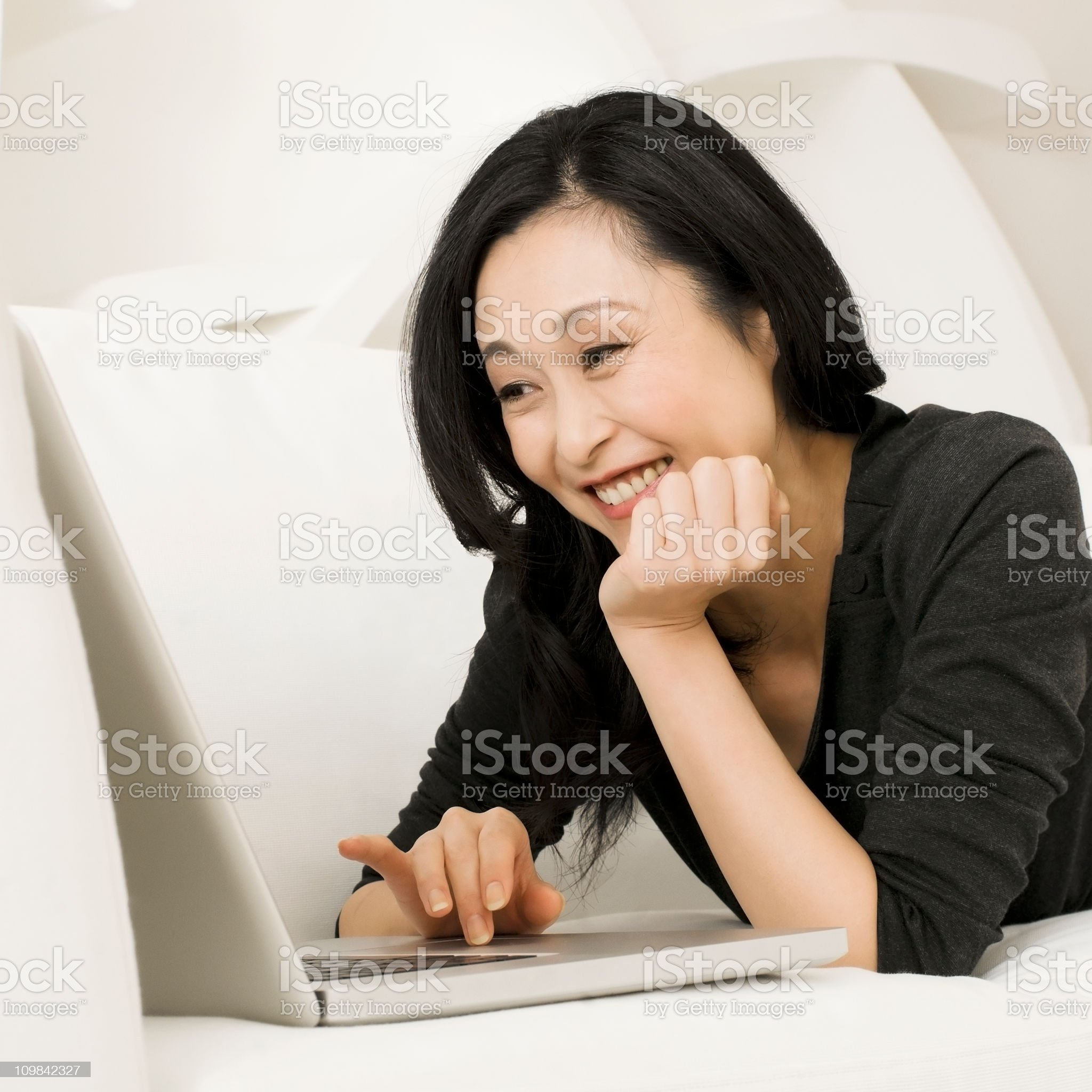Woman Lying on the Sofa and Using a Laptop royalty-free stock photo