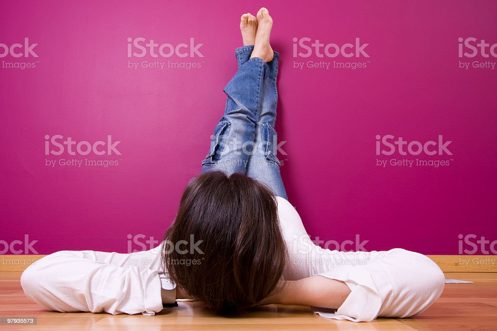 Woman lying on wooden floor with feet up on the pink wall stock photo