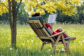 Woman lying outdoors in deck chair reading book