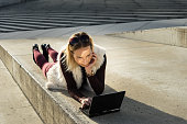 Woman lying outside on steps, holding laptop in city nature