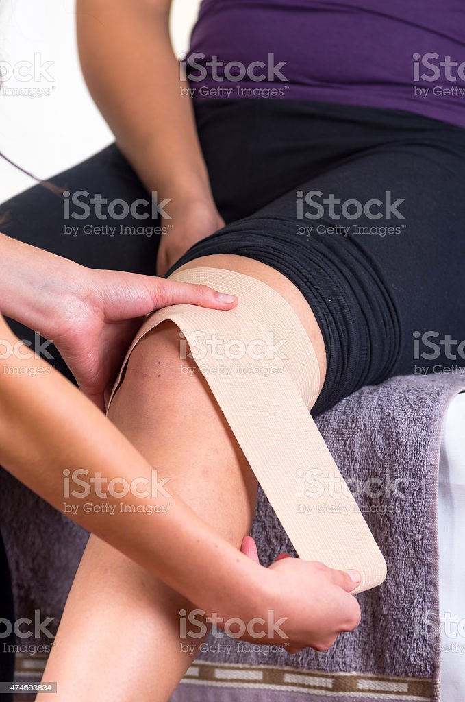 woman lying while getting a leg massage concept of physiotherapy stock photo