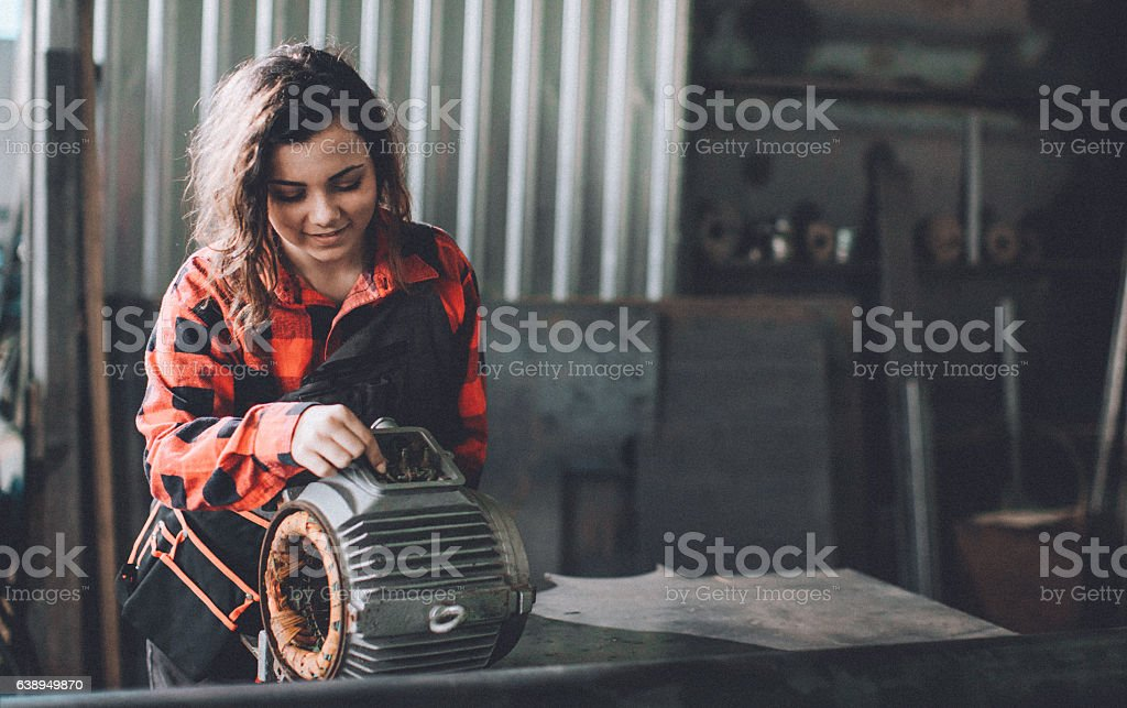 Woman machinist examining electric motor with voltmeter stock photo