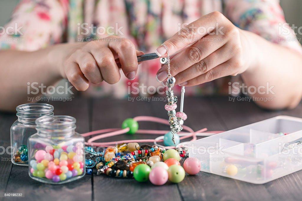 Woman make homemade bracelet stock photo