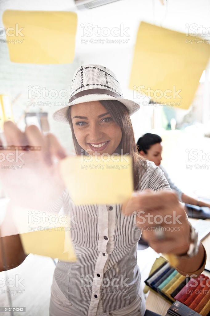 Woman make scheme on sticky notes on glass board stock photo