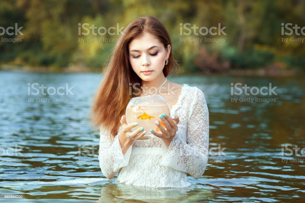 Woman makes a wish gold fish. stock photo