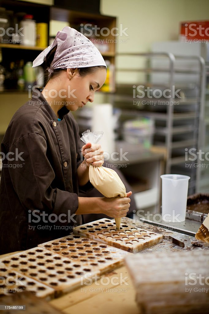 A woman makes chocolate bonbons in an industrial kitchen stock photo