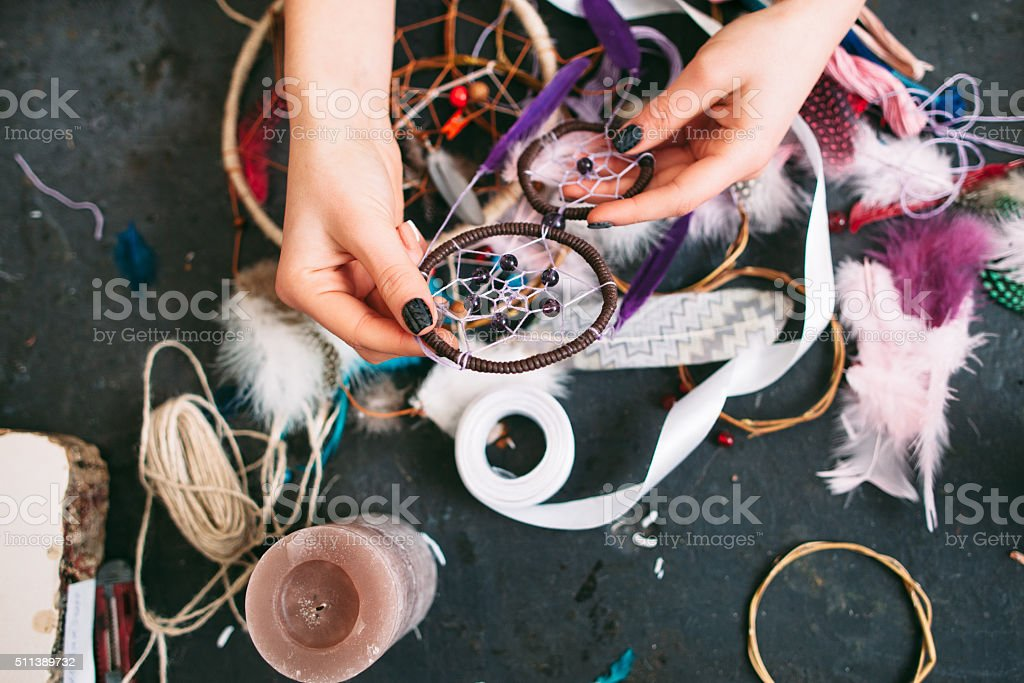 woman makes Dreamcatcher of sewing accessories. stock photo