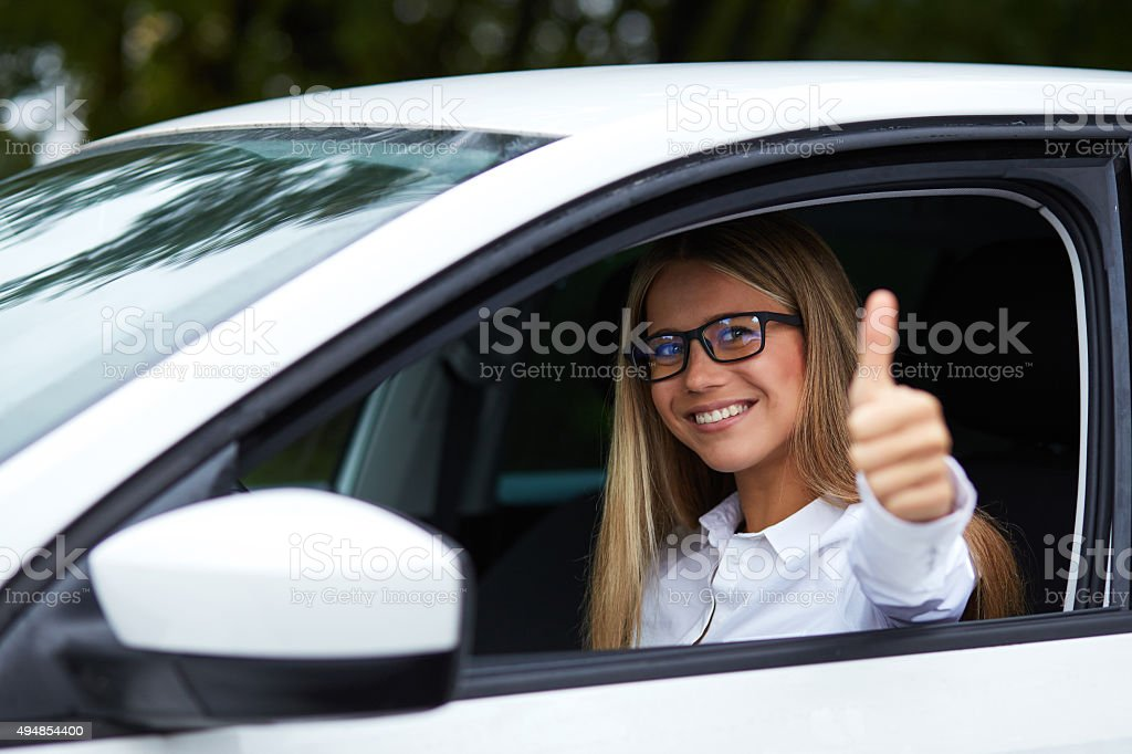 Woman makes gesture with thumb up stock photo