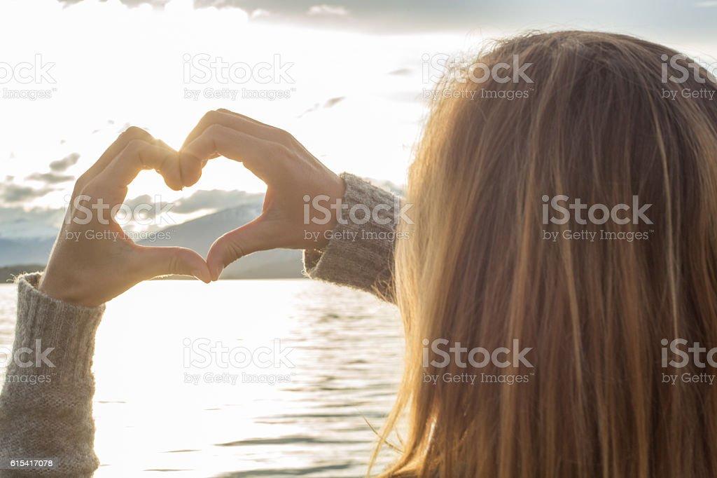 Woman makes heart shape finger frame on lake mountain landscape stock photo