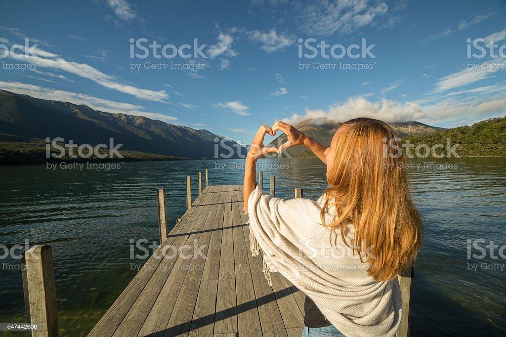 Woman makes heart shape finger frame on mountain lake landscape stock photo