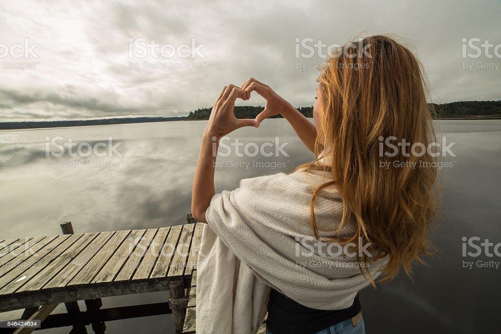 Woman makes heart shape finger frame to mountain lake landscape stock photo