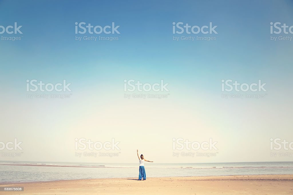 woman makes meditation exercises facing the sea stock photo