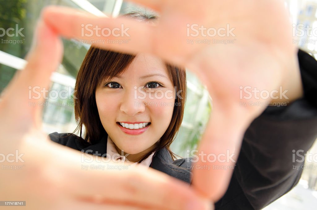 Woman making a box frame with her fingers stock photo