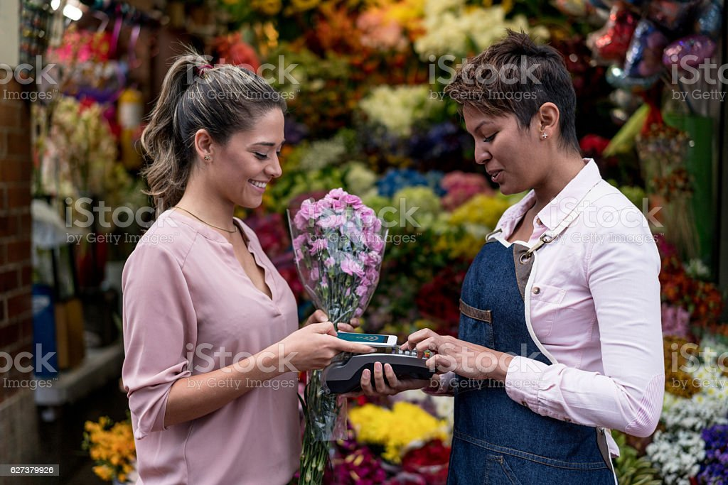Woman making a contactless payment at the florist stock photo