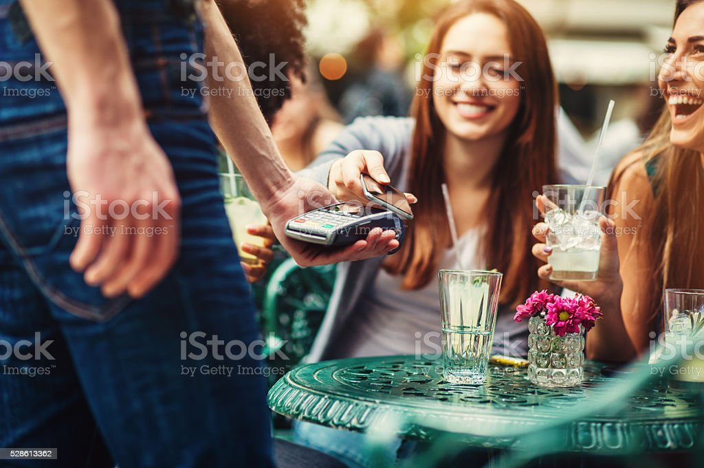 Woman making a contactless payment with her phone stock photo