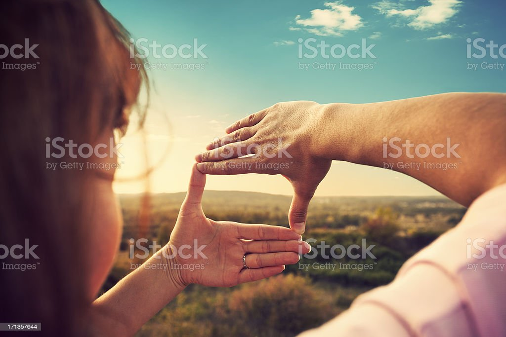 Woman making a frame with her hands while outside stock photo