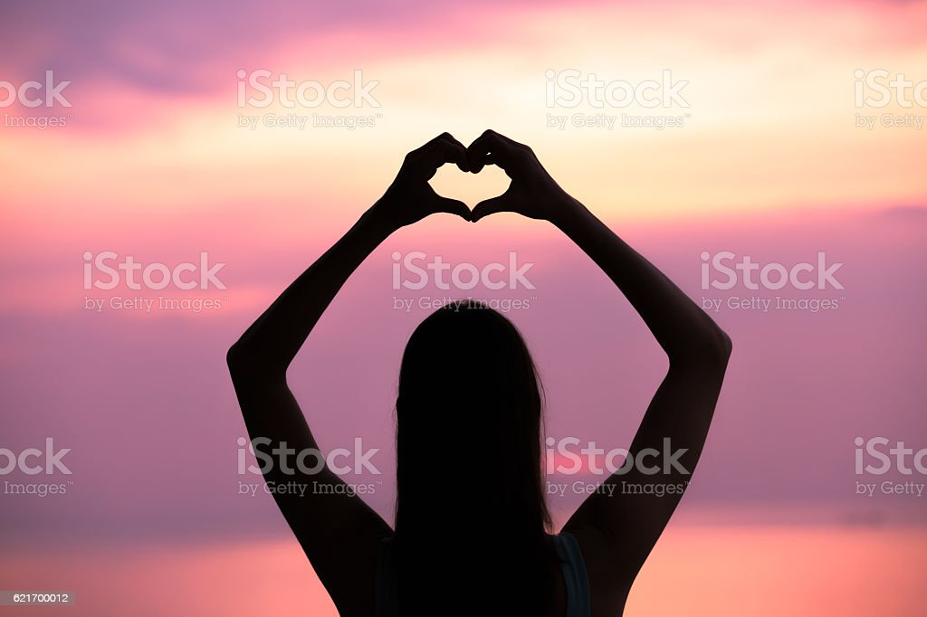 Woman making a hand shaped heart at sunset. stock photo