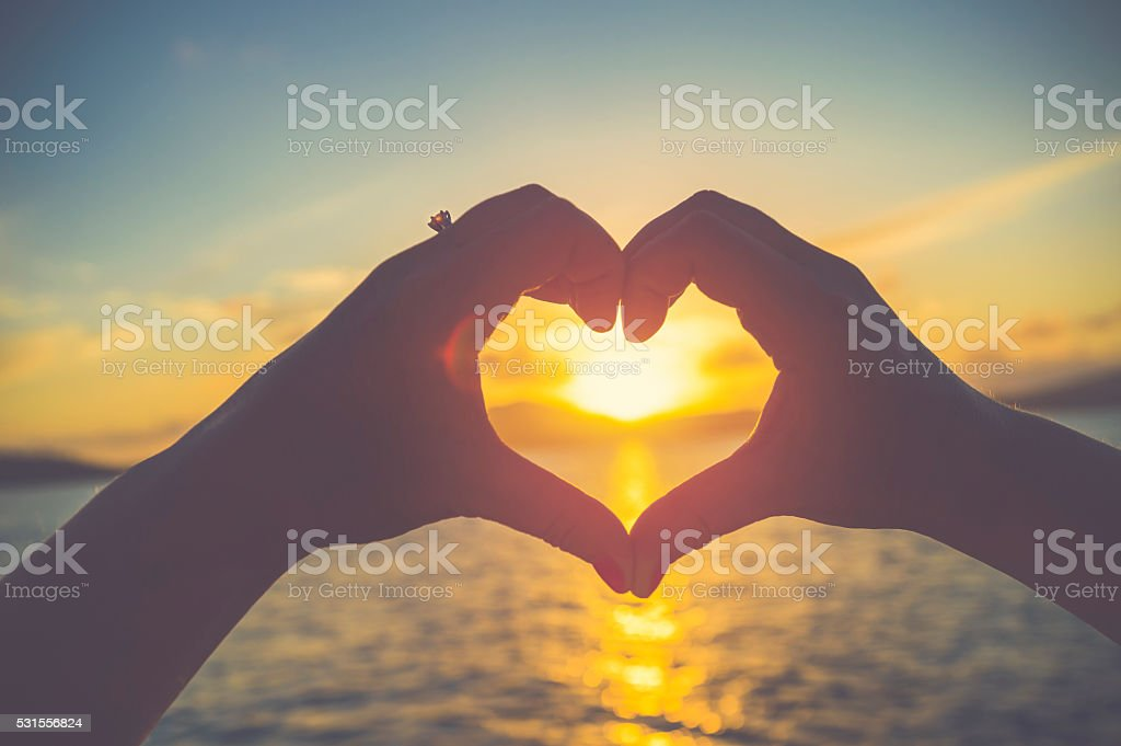 Woman making a heart shape with her hands. stock photo