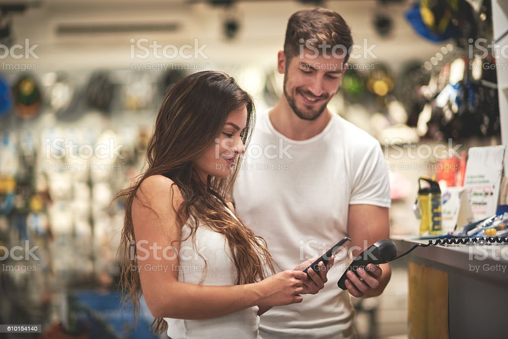 Woman making a payment in bicycle store stock photo