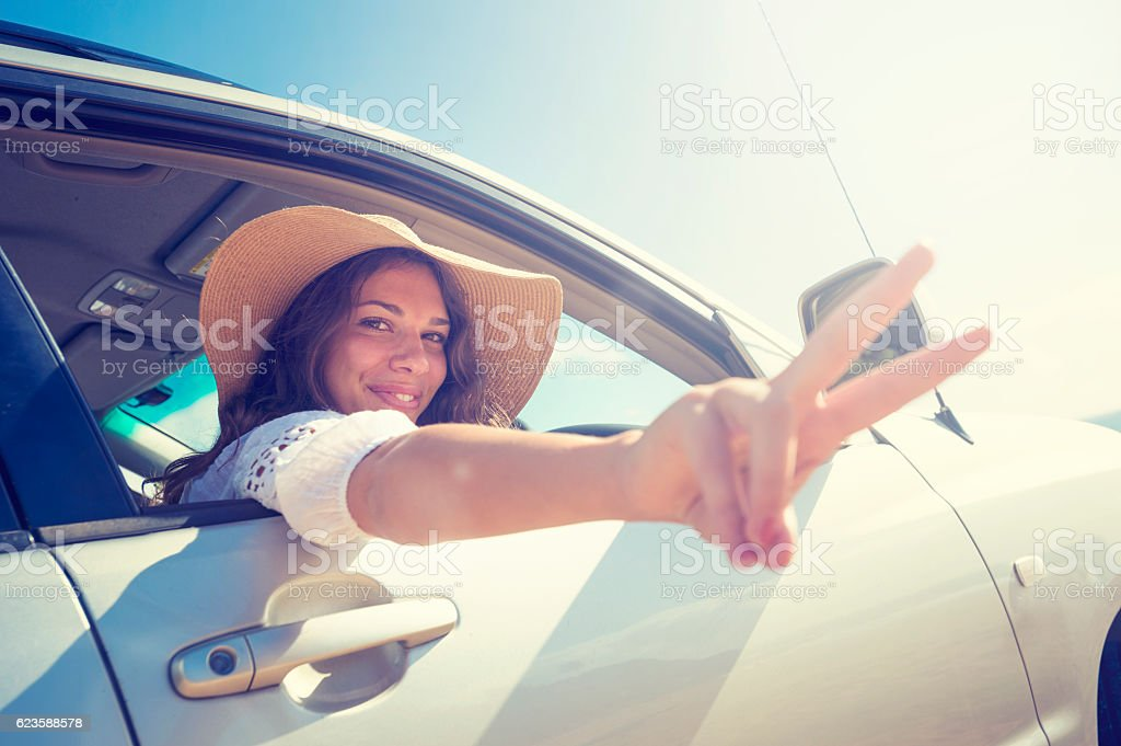 Woman making a peace sign while driving stock photo