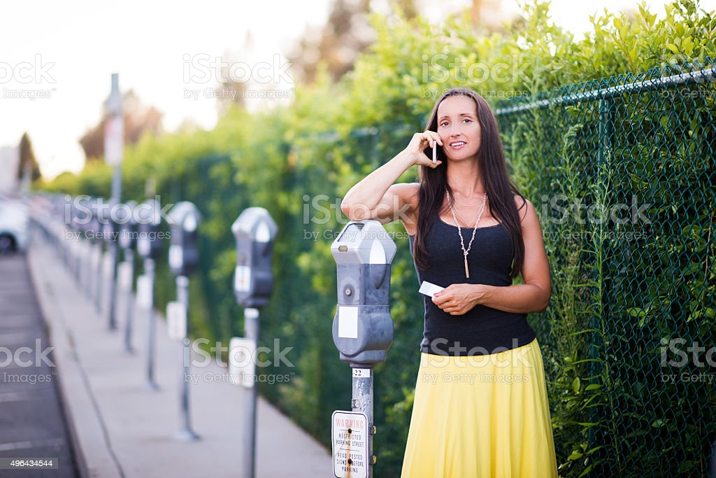 Woman making a phone call next to parking meter stock photo