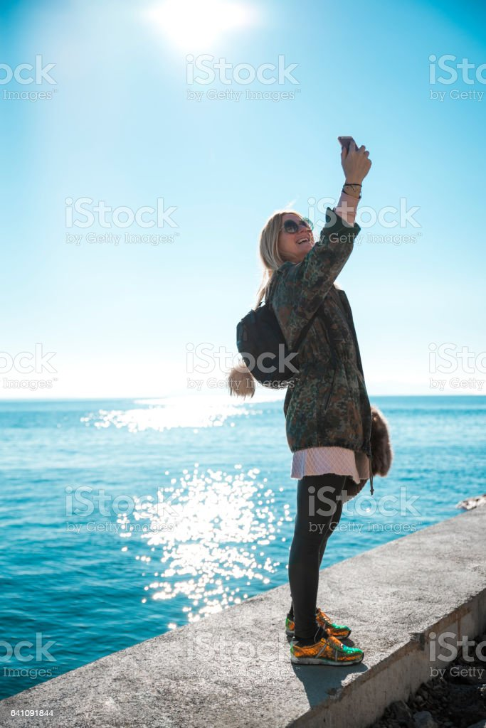 Woman making a selfie by the sea stock photo