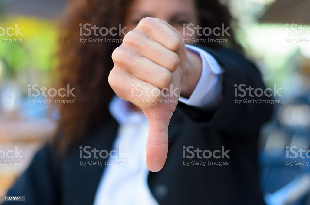 Woman making a thumbs down gesture stock photo