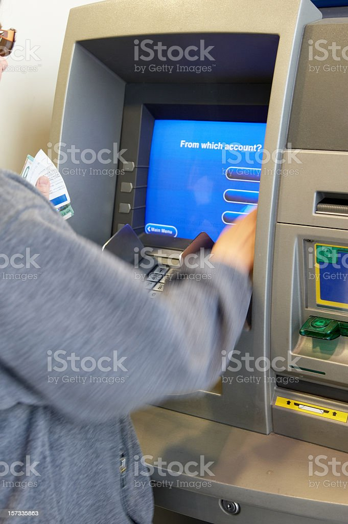 Woman making ATM withdrawal a royalty-free stock photo
