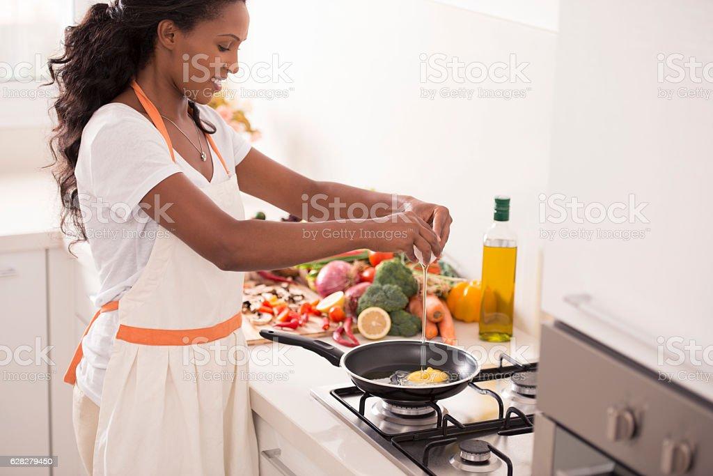Woman making breakfast at kitchen. stock photo