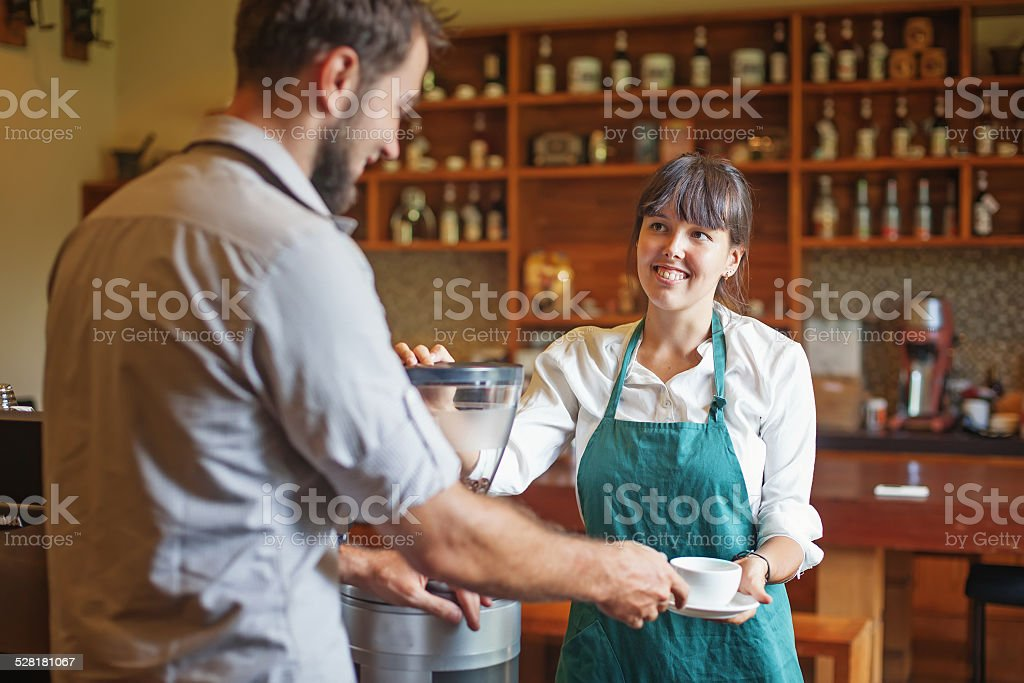 woman making coffee and giving it to customer stock photo