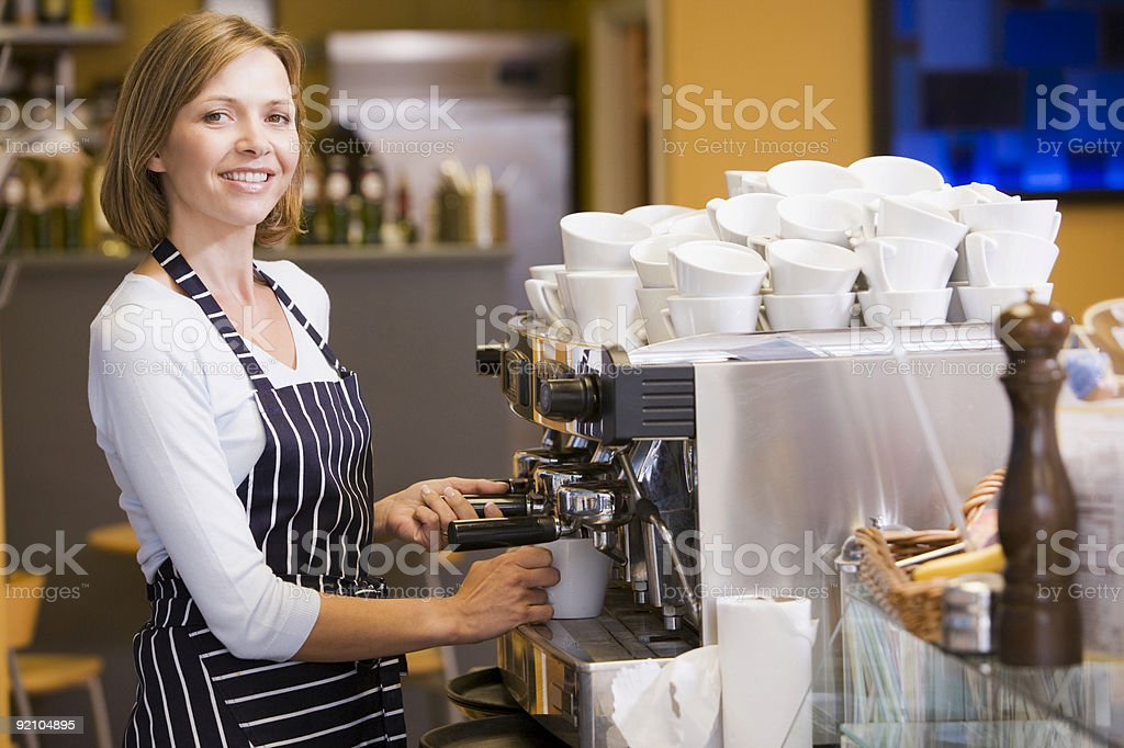 Woman making coffee in restaurant smiling royalty-free stock photo