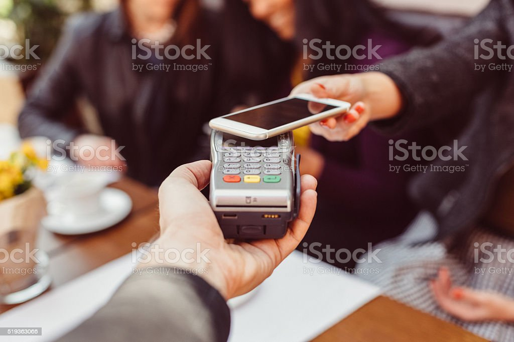 Woman making contactless payment with smartphone stock photo