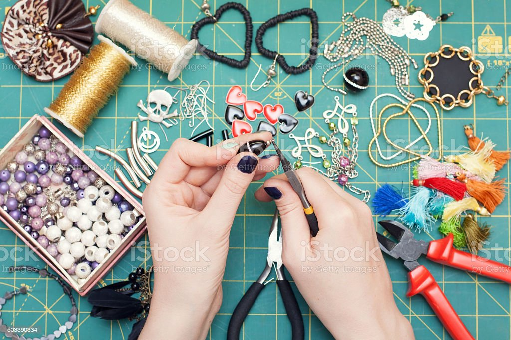 Woman making costume  jewelry, earrings stock photo
