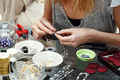 Woman making costume jewelry. Home made. Blurred foreground.