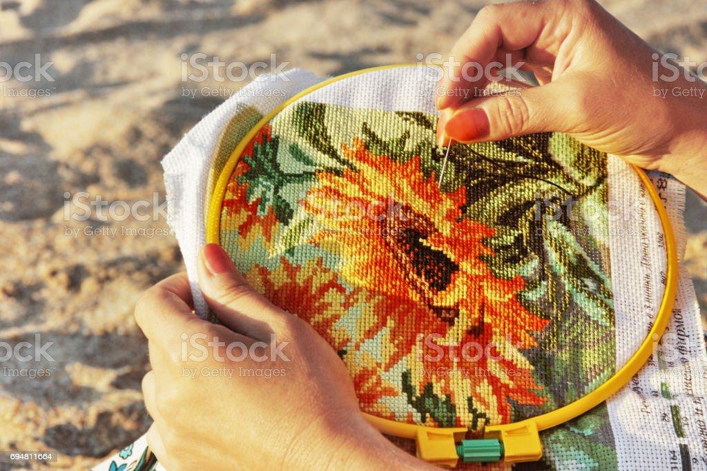 Woman making cross-stitch  embroidery. stock photo