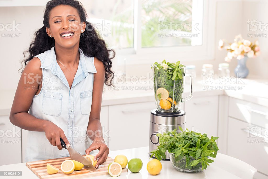 Woman making fresh lemonade, using blender at home kitchen. stock photo