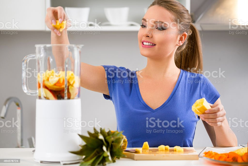 woman making fruits smoothies with juicer machine stock photo