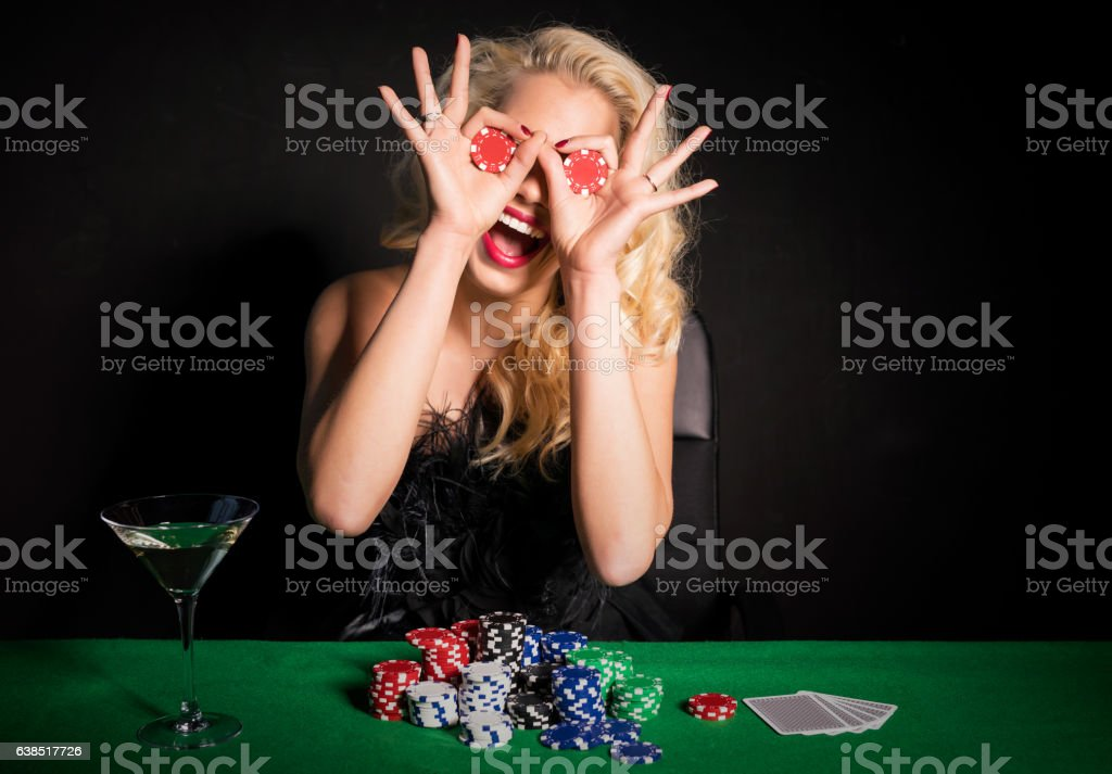 Woman making funny face with poker chips stock photo