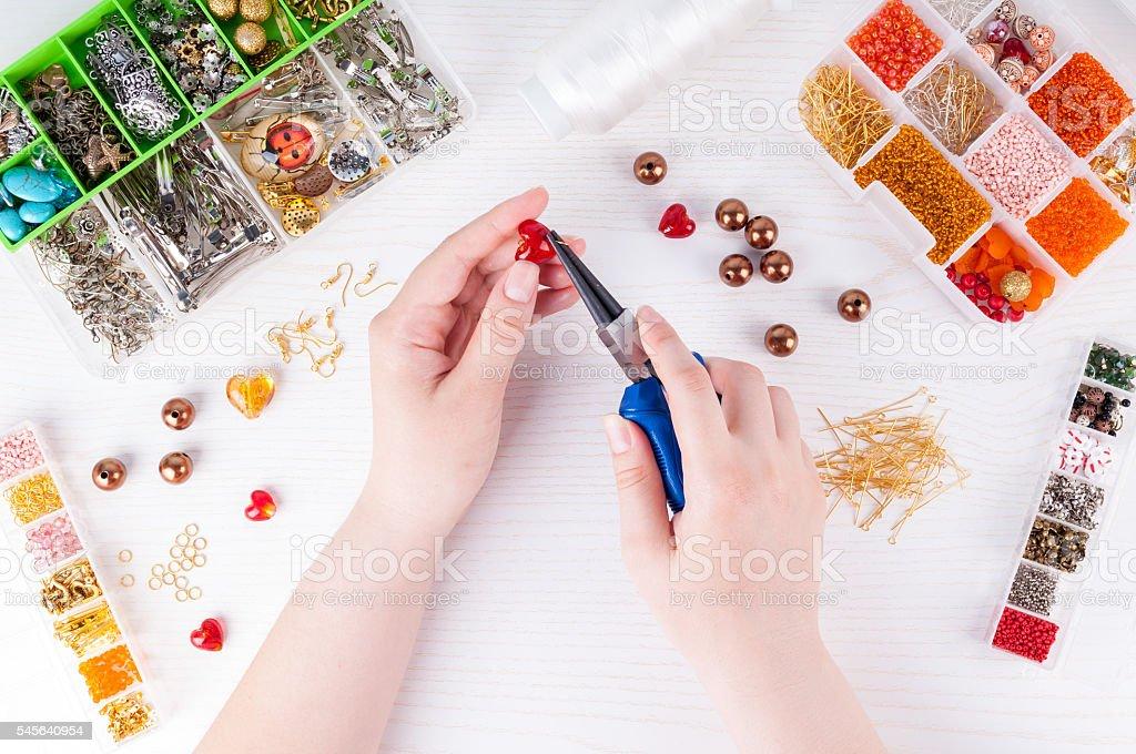Woman making handmade jewellery. Handmade accessories. Top view stock photo