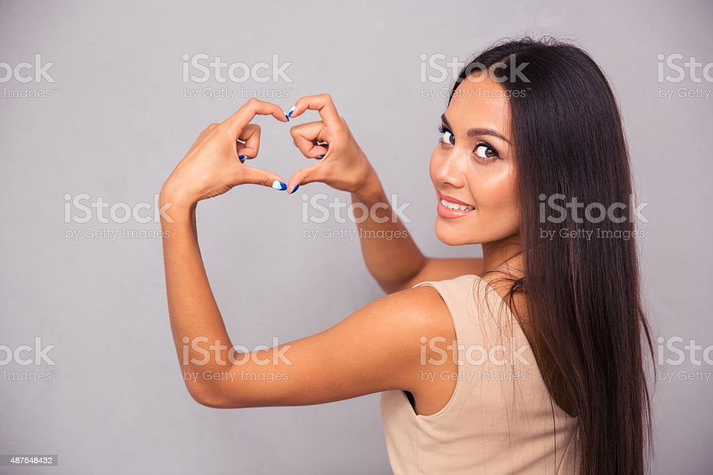 Woman making heart gesture with fingers stock photo
