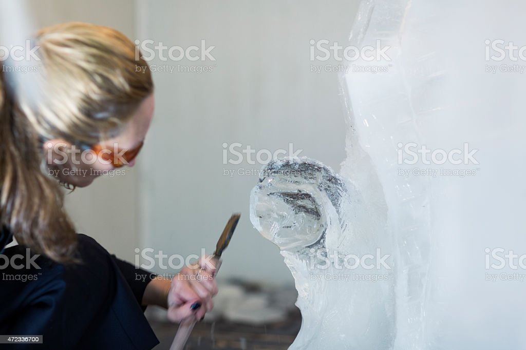 Woman Making Ice sculpture. stock photo