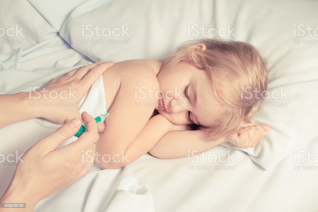 woman making injection by syringe in child stock photo