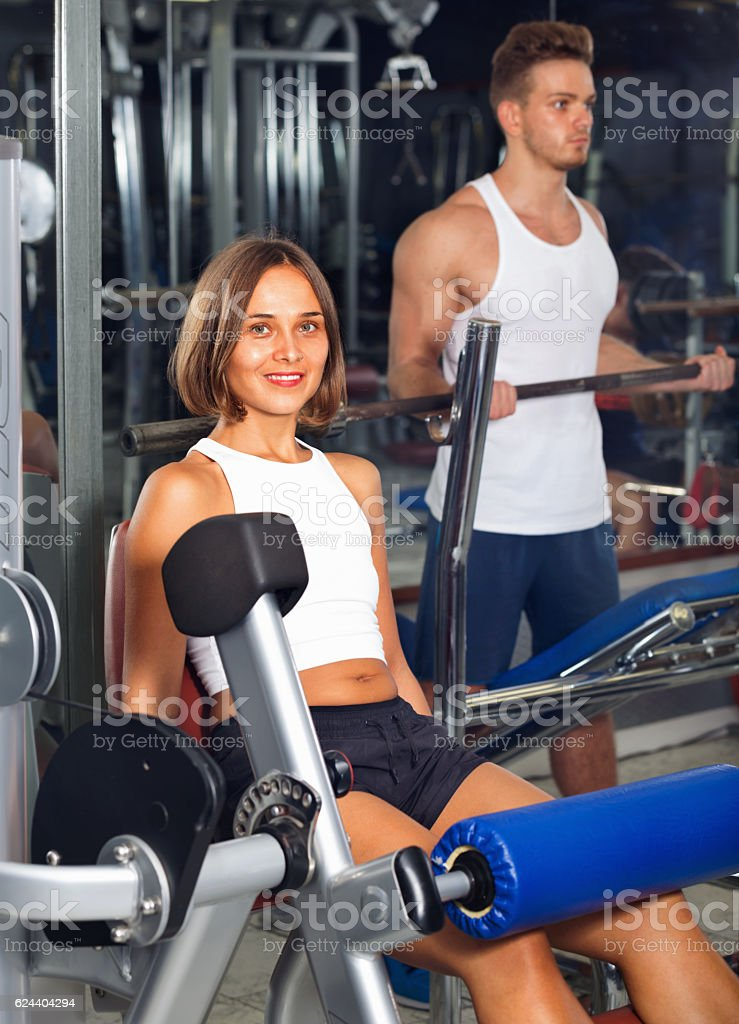 Woman making leg extension exercise using gym machinery stock photo