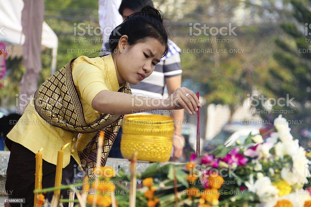 Woman Making Merit with Joss Sticks in Laos stock photo