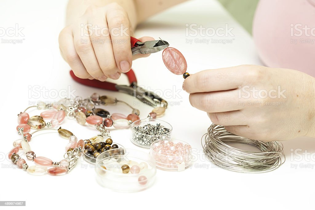 Woman making necklase from colorful plastic beads stock photo
